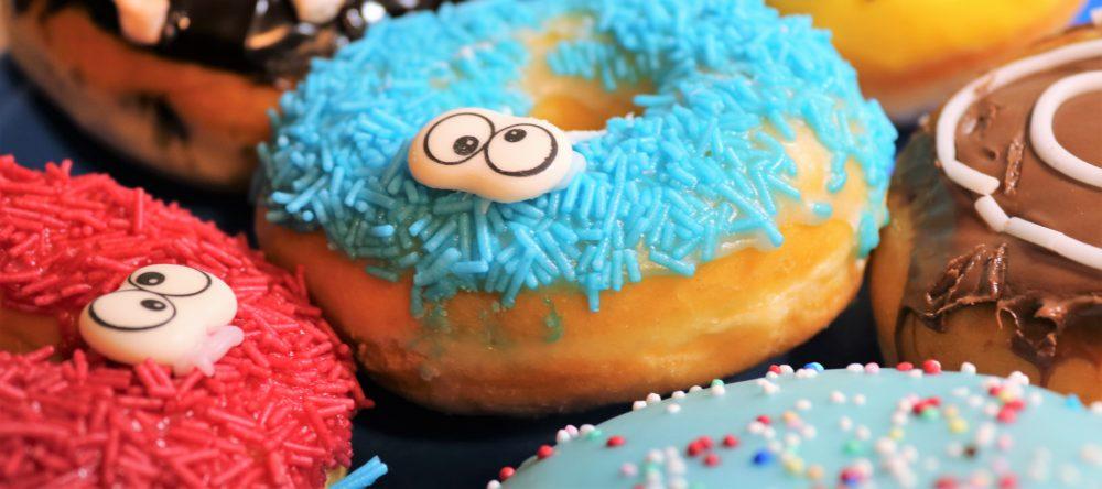 Bunte Donuts liegen nebeneinander. Zwei Donuts haben Zuckeraugen, die etwas verdreht sind und aussehen, als ob sie schielen.