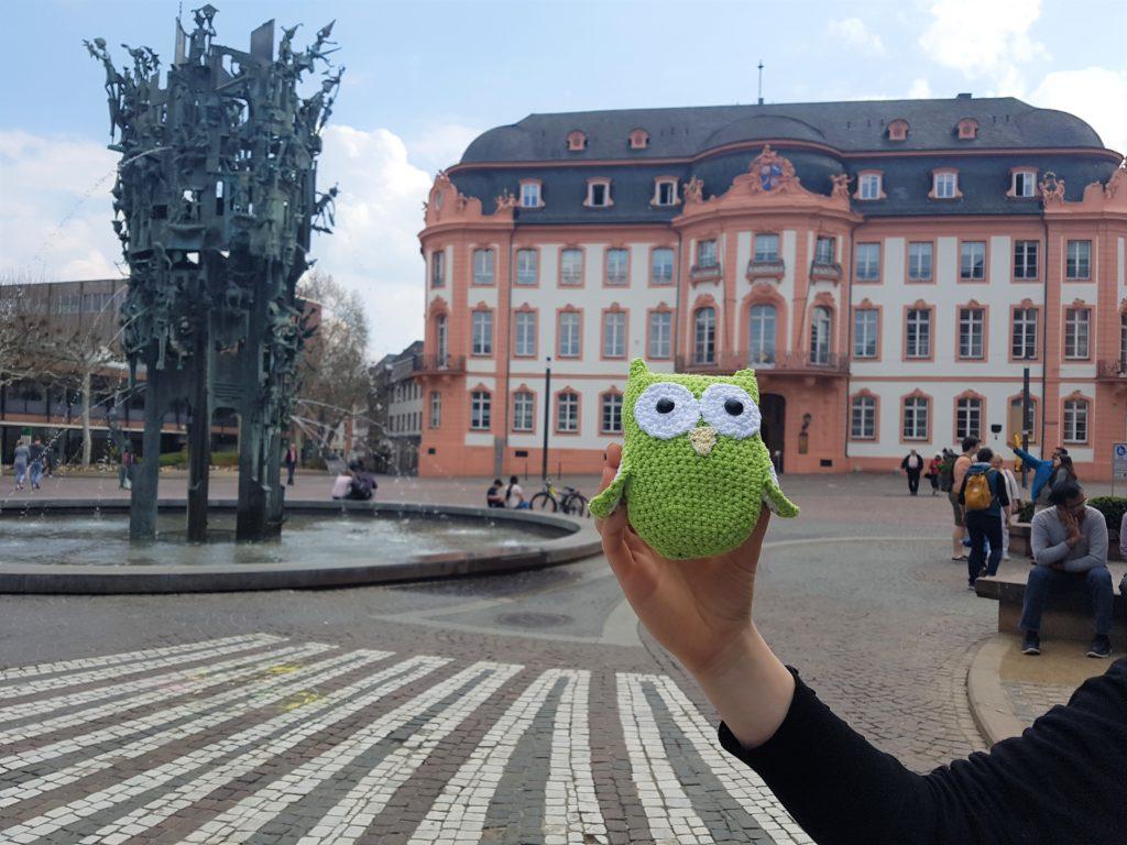 Die Eule ist im Vordergrund. Im Hintergrund sieht man den Schillerplatz in Mainz.