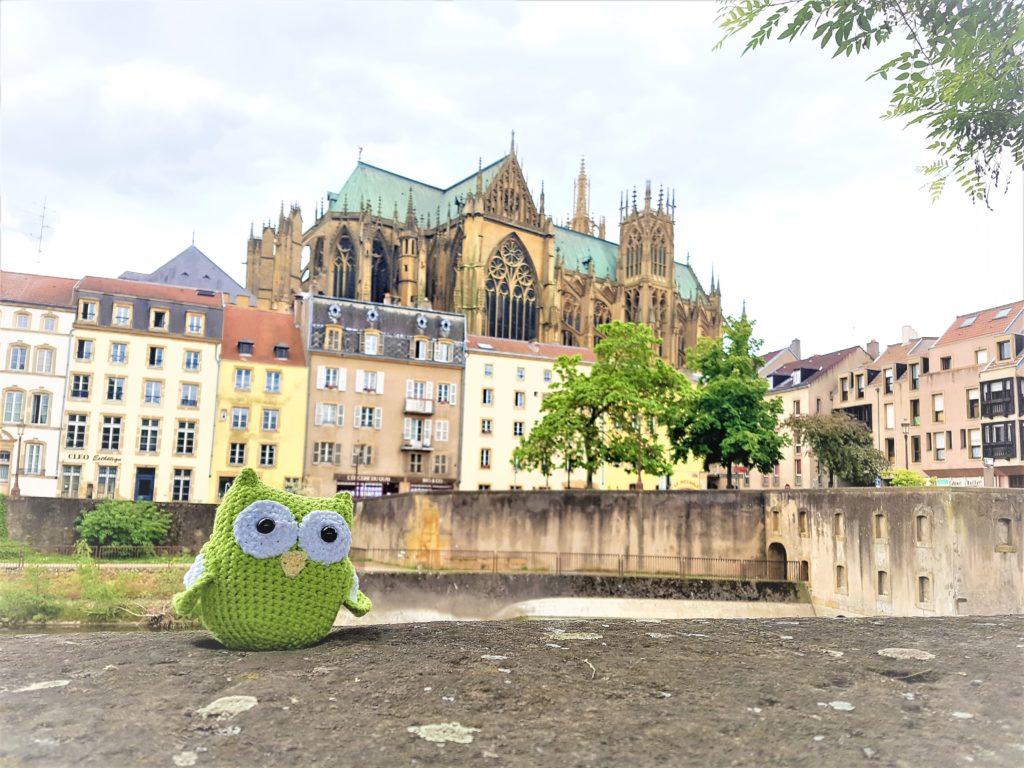 Eine gehäkelte Eule sitzt auf einer Mauer. Im Hintegrund sieht man alte Häuser und eine große Kathedrale.