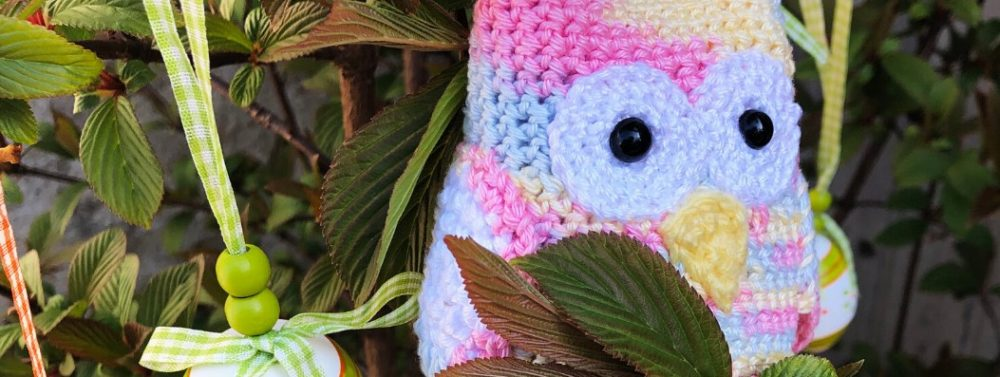 Ein buntes Eulen-Maskottchen sitzt in einem Oster-Strauß