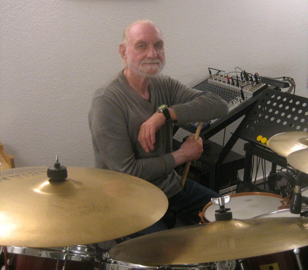 Ein älterer Herr mit Bart sitzt an einem Schlagzeug und lehnt mit einen Arm auf einem der Sticks.