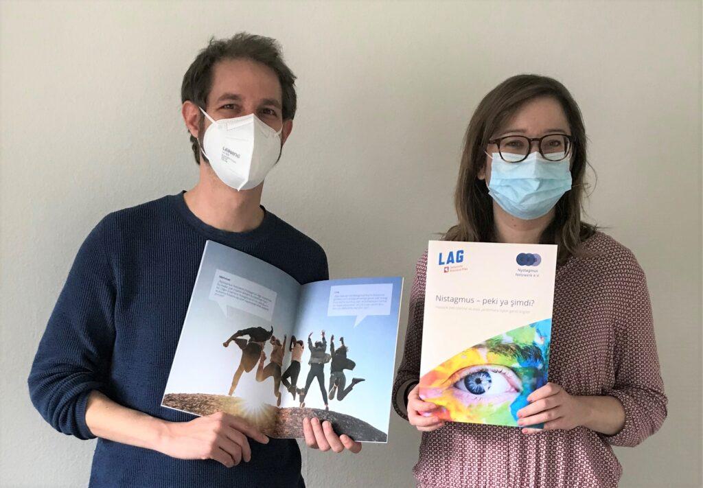 Auf dem Bild sieht man einen Mann und eine Frau. Beide haben braune Haare und eine medizinische Maske auf. Sie halten eine bunte Broschüre in den Händen.