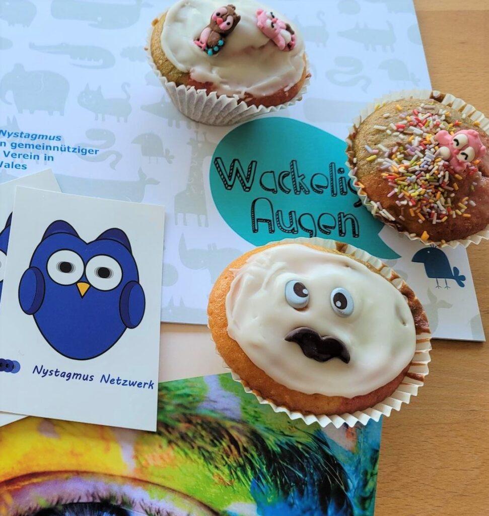 Es sind drei bunte Muffins und Broschüren vom Verein zusehen. Ein Muffin hat Zuckeraugen, die in verschiedene Richtungen schauen.